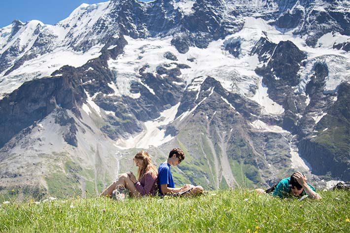 Students reading below the mountains
