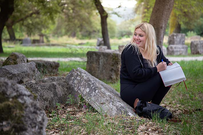 Student journaling in the Ruins of Olympia