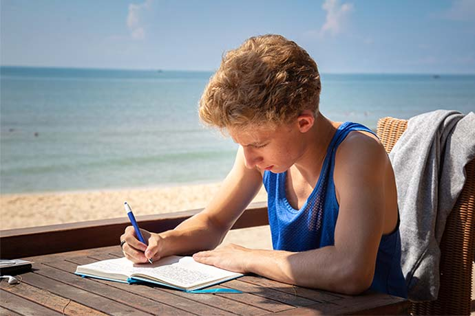 Student studying on the beach